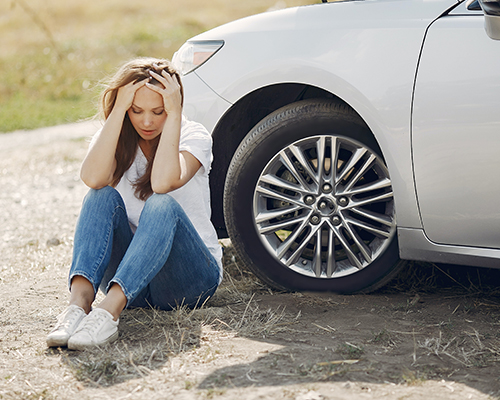 woman sitting by a car holding her head in distress